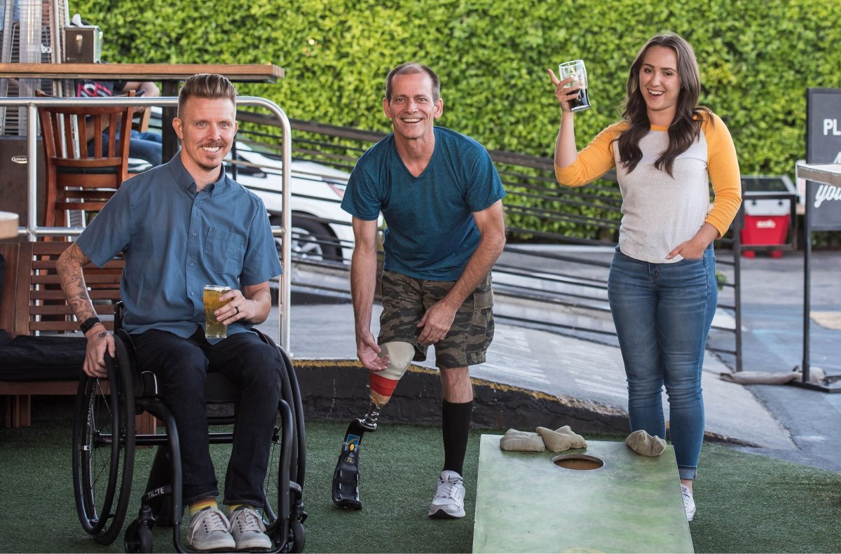 A man in a wheelchair, a man with a prosthetic leg, and a woman drinking beer and playing cornhole.