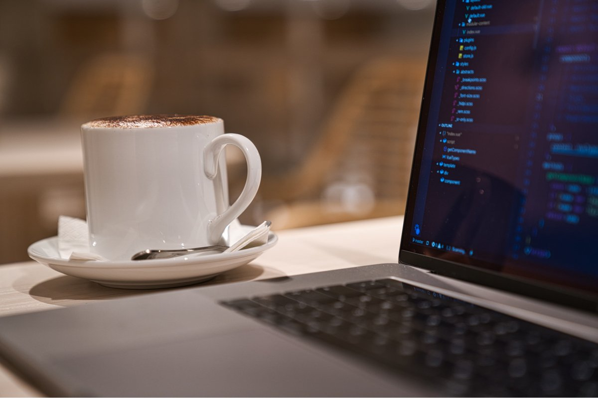 A photo of white coffee mug on a saucer next to a laptop on a cafe table.