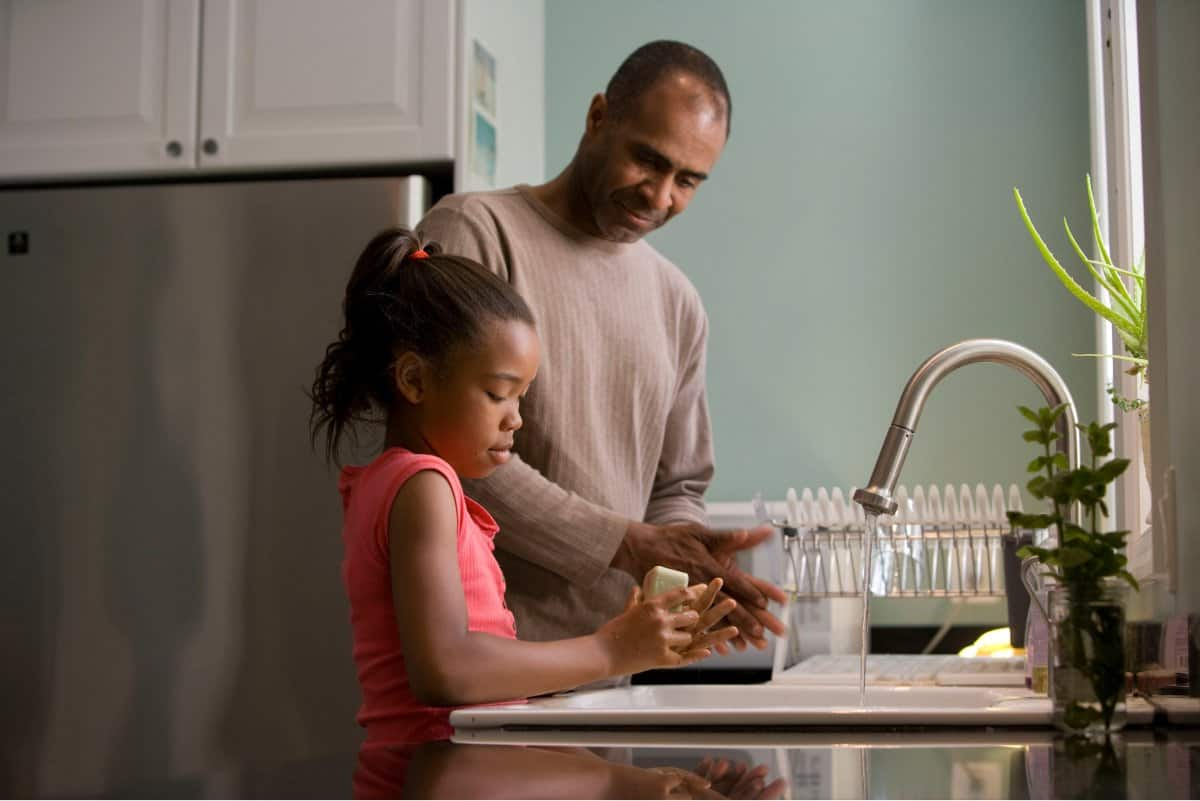 A photo of a father and daughter washing their hands together at the kitchen sink.