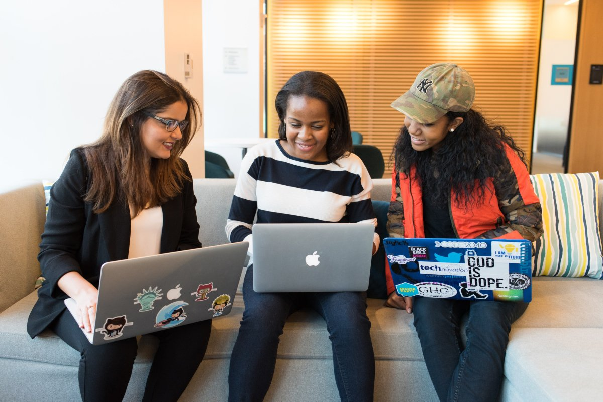 A photo of three women sitting next to each other on a couch conferring over a project, each with a laptop in their laps.