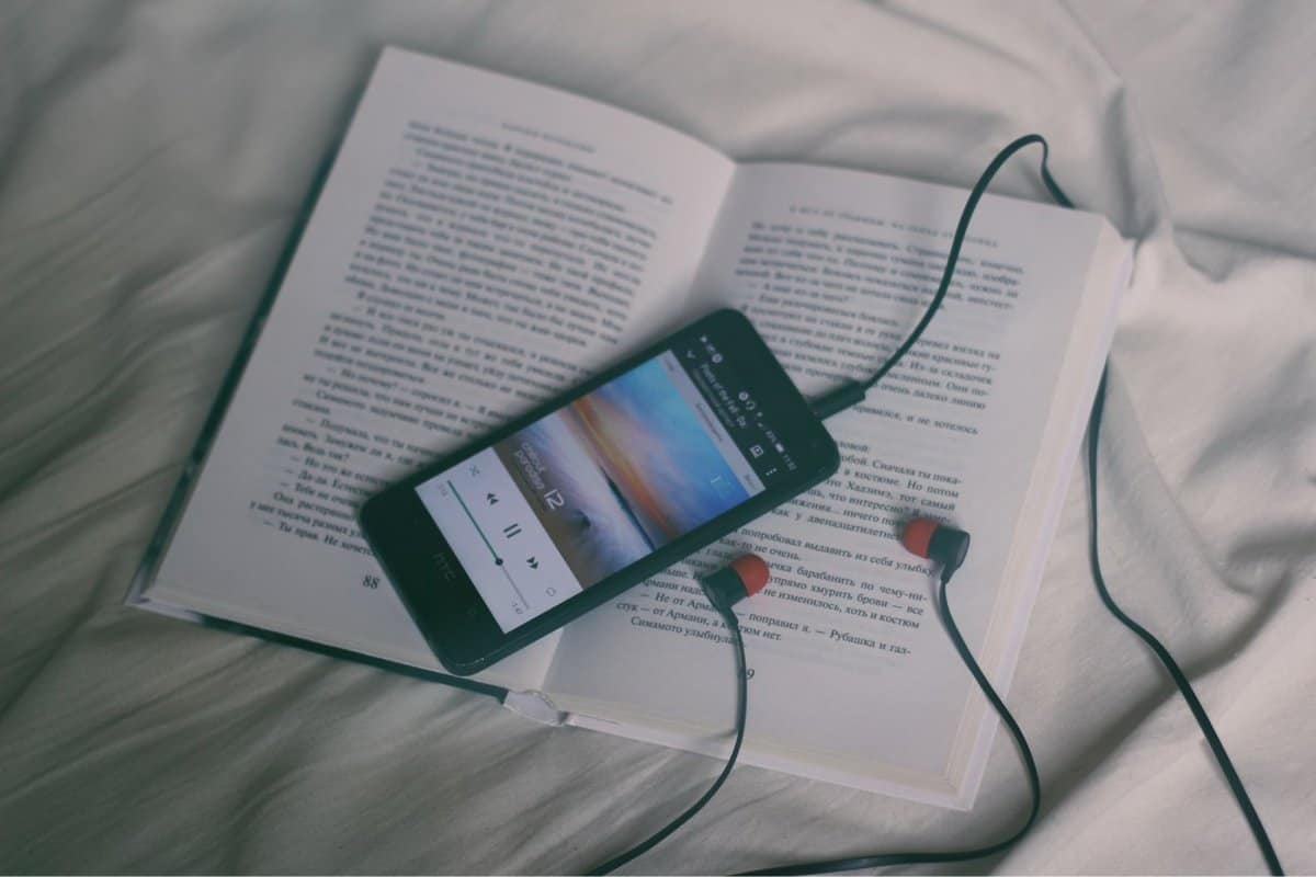 A photo of a smartphone and a set of earbuds resting on an open book.