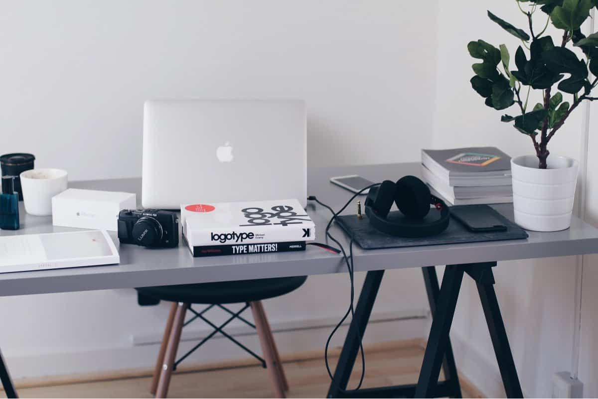 A photo of a mobile app designer's desk, featuring a laptop, camera, and books about font face.