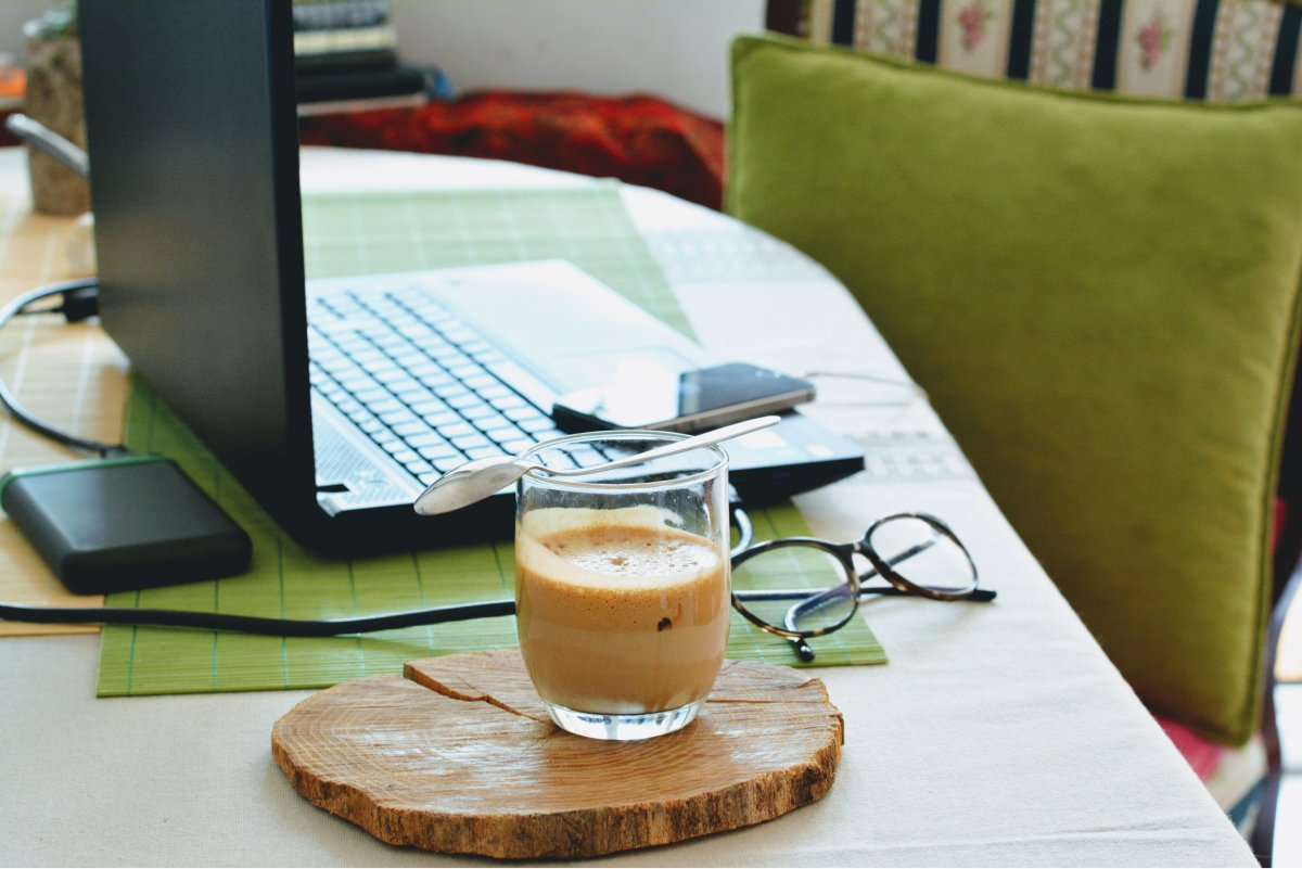 A photo of someone's remote work station, complete with a laptop and a latte.