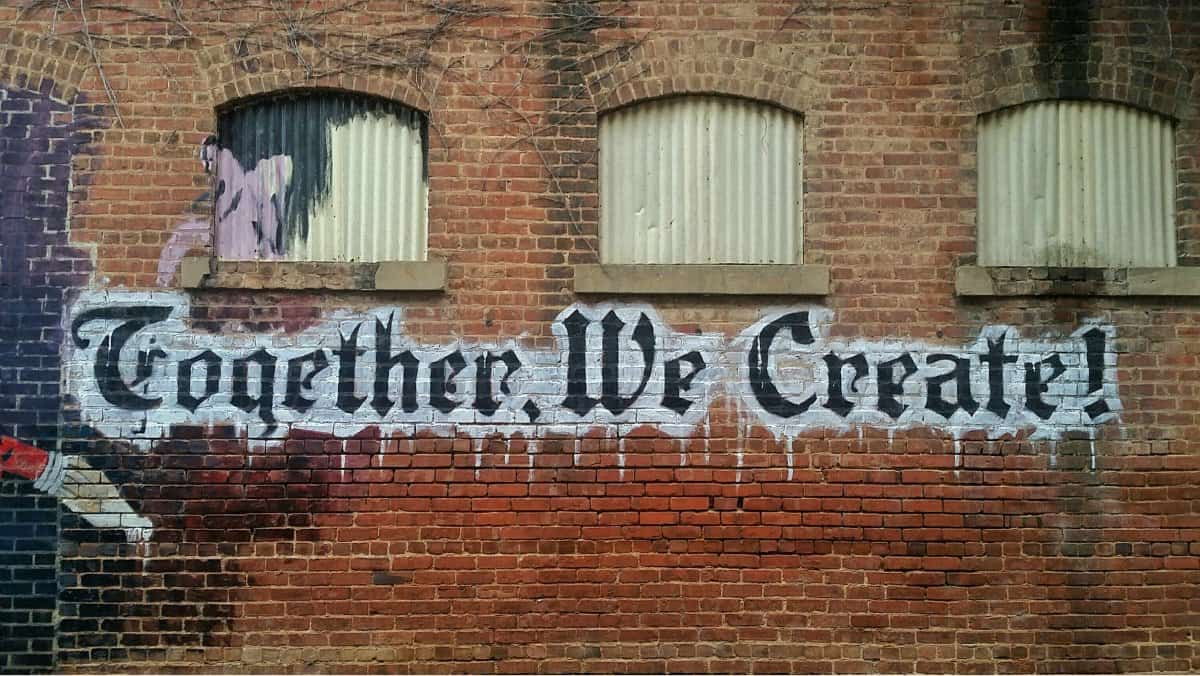 """A photo of a graffiti sign on a brick building that says """"Together, We Create!"""""""