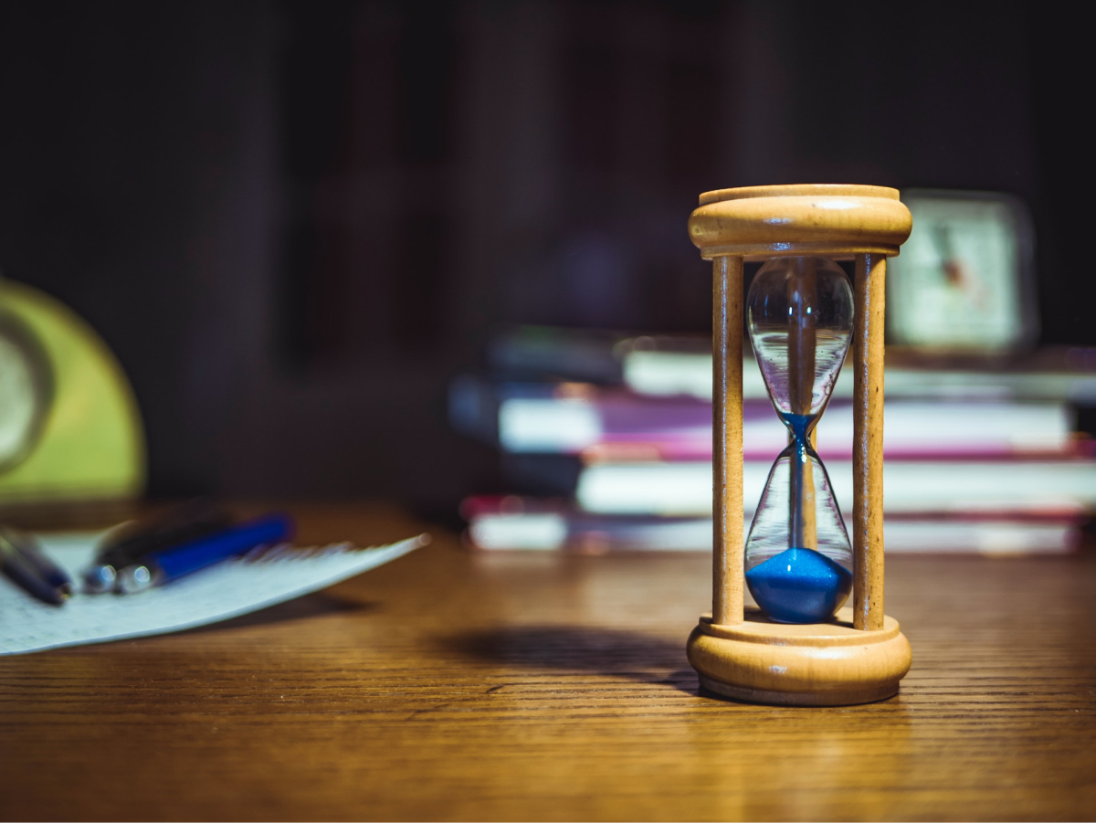 An hourglass sitting on a desk with books and pens in the background.