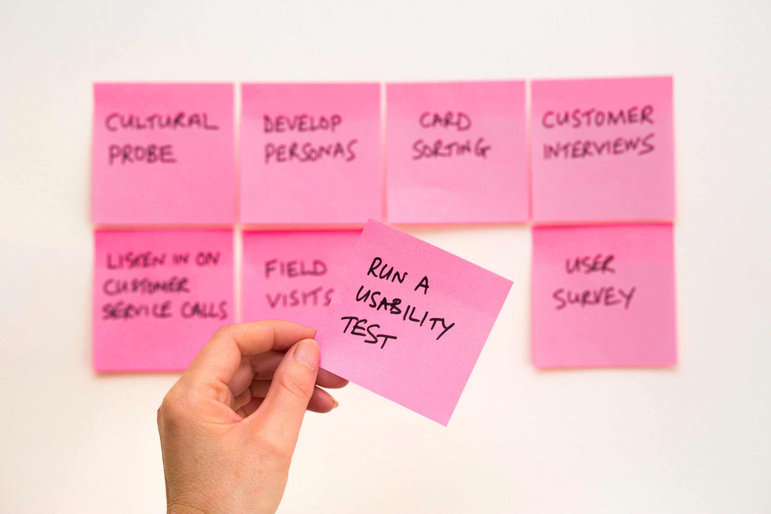 """A bunch of pink Post-It notes, with one in focus saying """"Usability Test"""""""