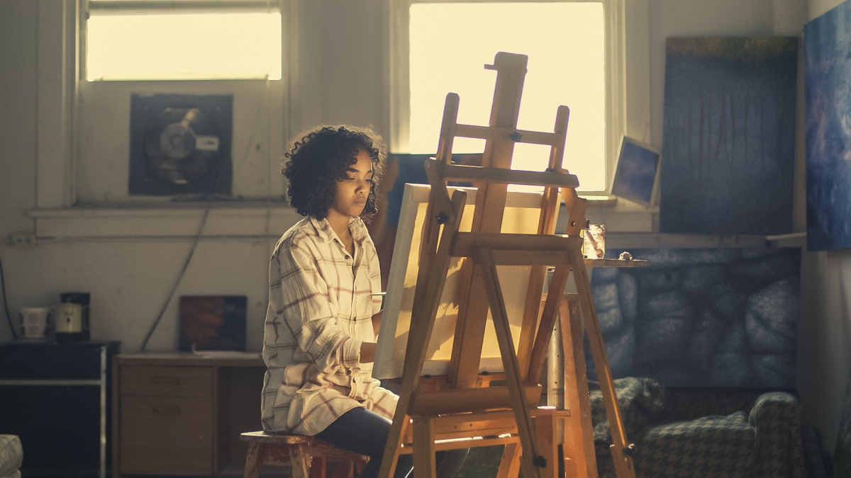 A woman focusing on her painting bathed in warm light.