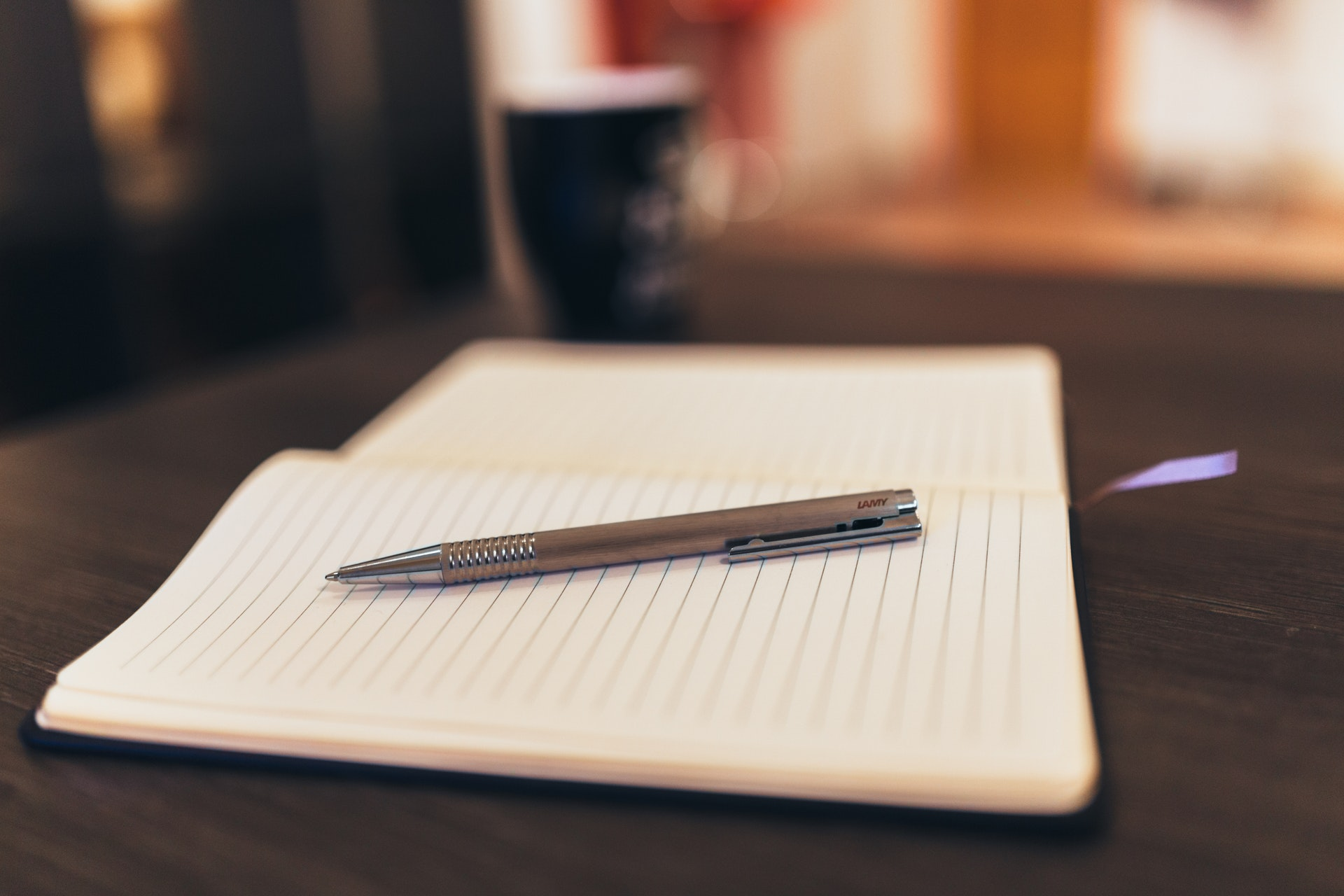 A blank lined notebook and a pen sitting on a desk.