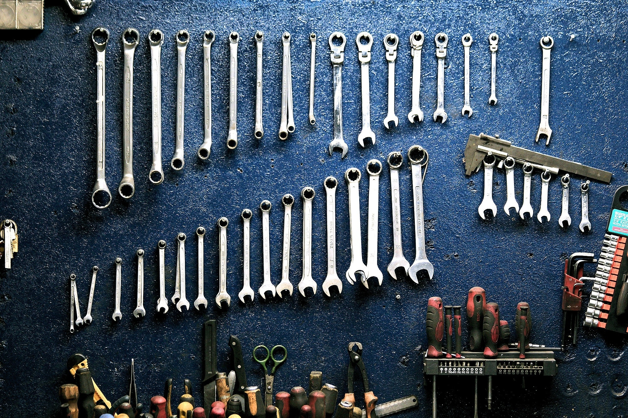 Wrenches and other tools hung up on a blue wall.