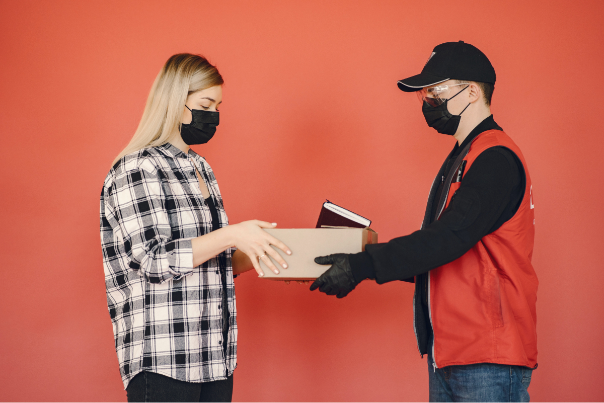 A delivery man handing a boss to a customer.