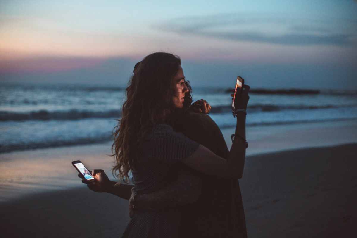 Two people embracing on a beach while looking at their smartphones.