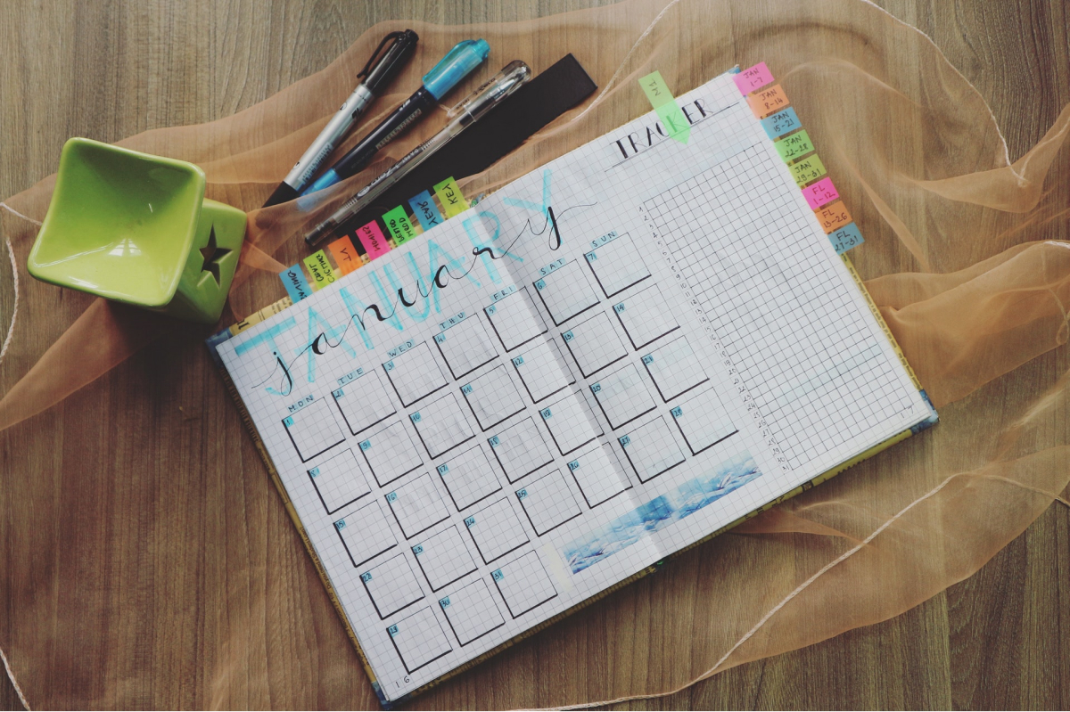 A calendar with colorful stickies and pens on a wood surface.
