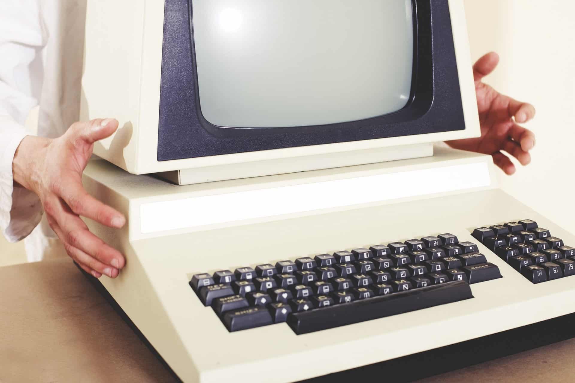 A person holding a large old school computer.