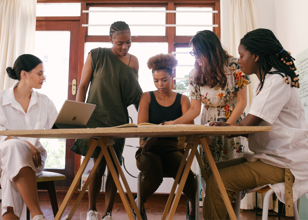 Five women around a table performing a creative idea review.
