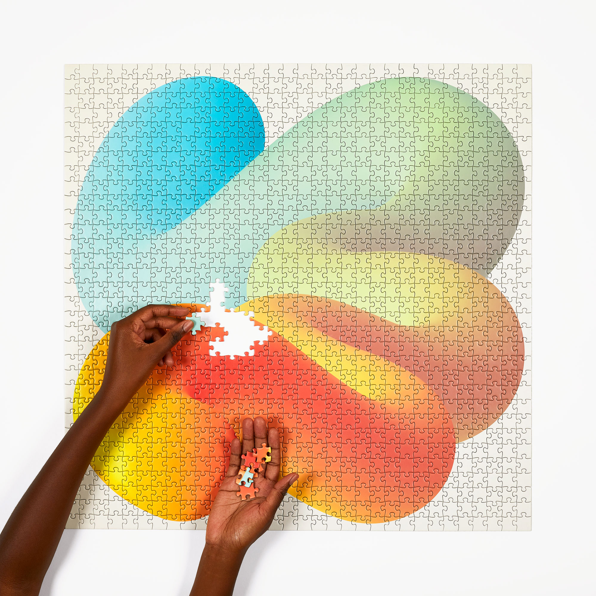 A person completing a colorful puzzle by Four Point Puzzles.