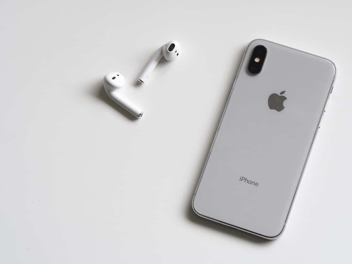 A pair of Airpods and an iPhone face down on a table.