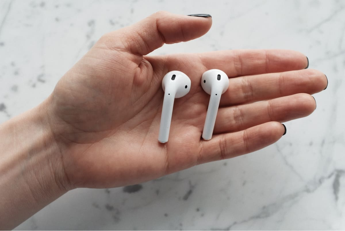 A person's hand with a pair of AirPods in them.