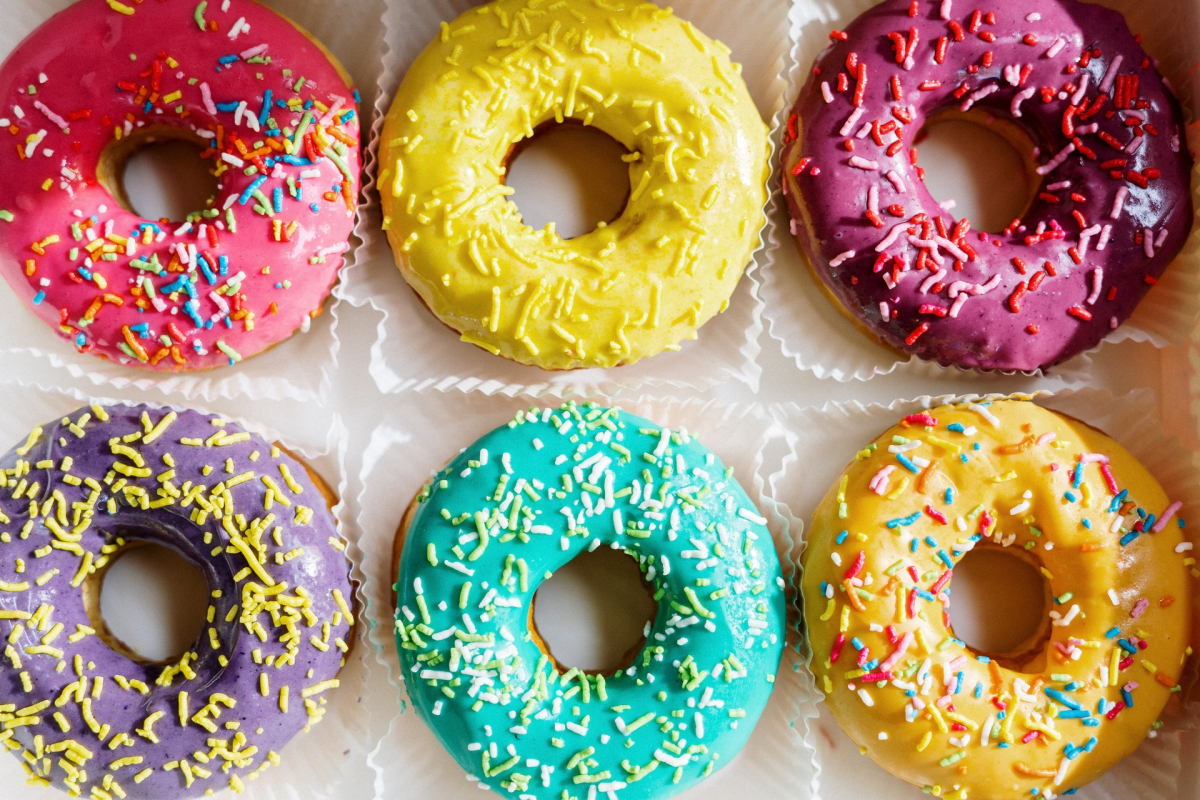Six colorful donuts with sprinkles.