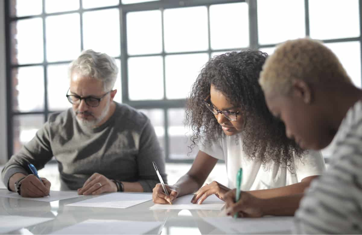 Three people taking notes at a table in a bright room.