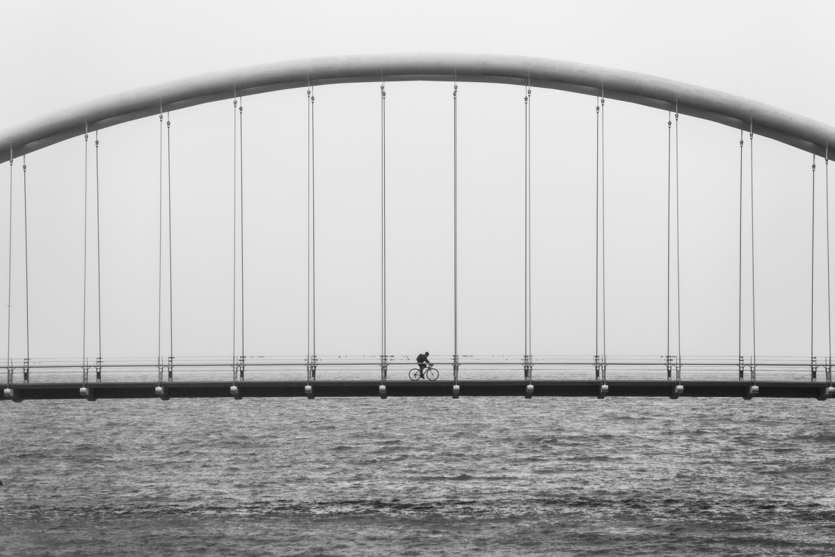 A person riding a bike over a bridge.