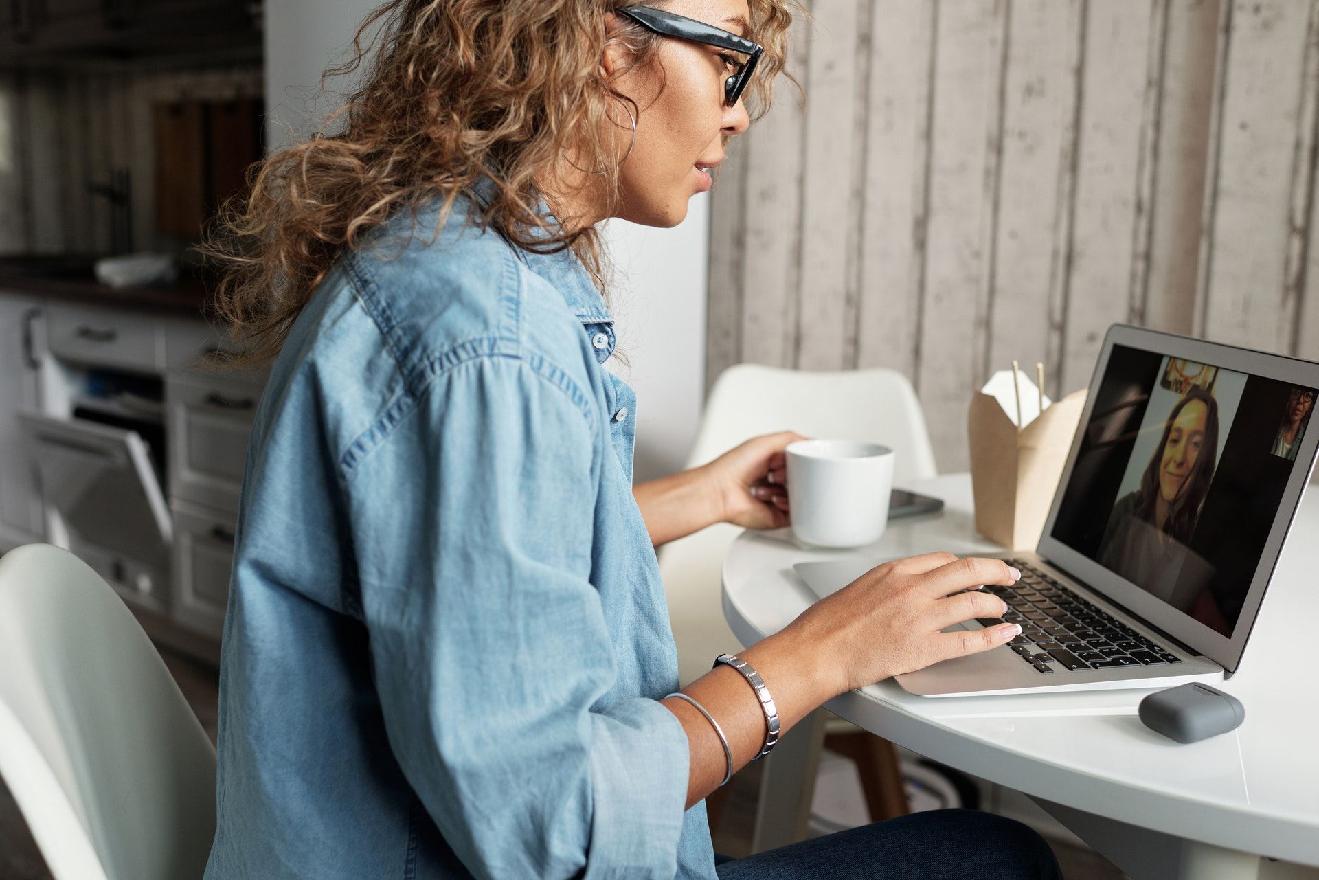 A woman sitting at a table on a video call.