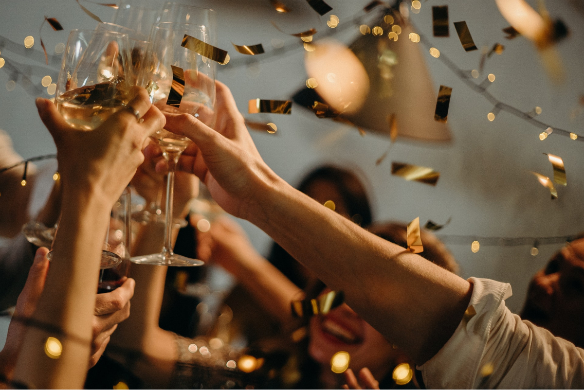 Several people raising their glasses to cheers as confetti falls.