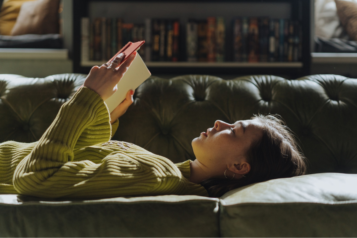 A woman laying on a couch, reading a design theory book.