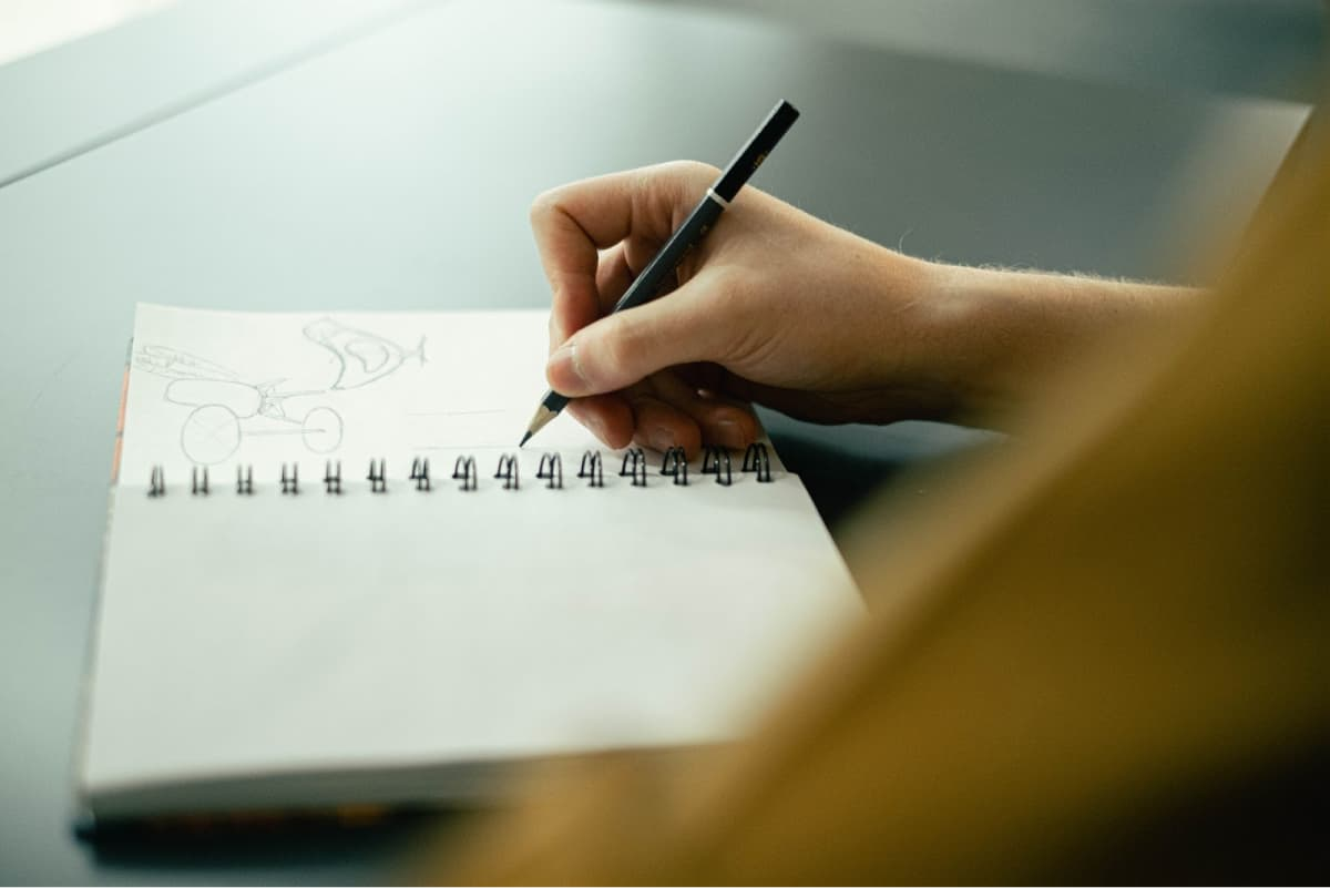 A person sketching in a notebook.