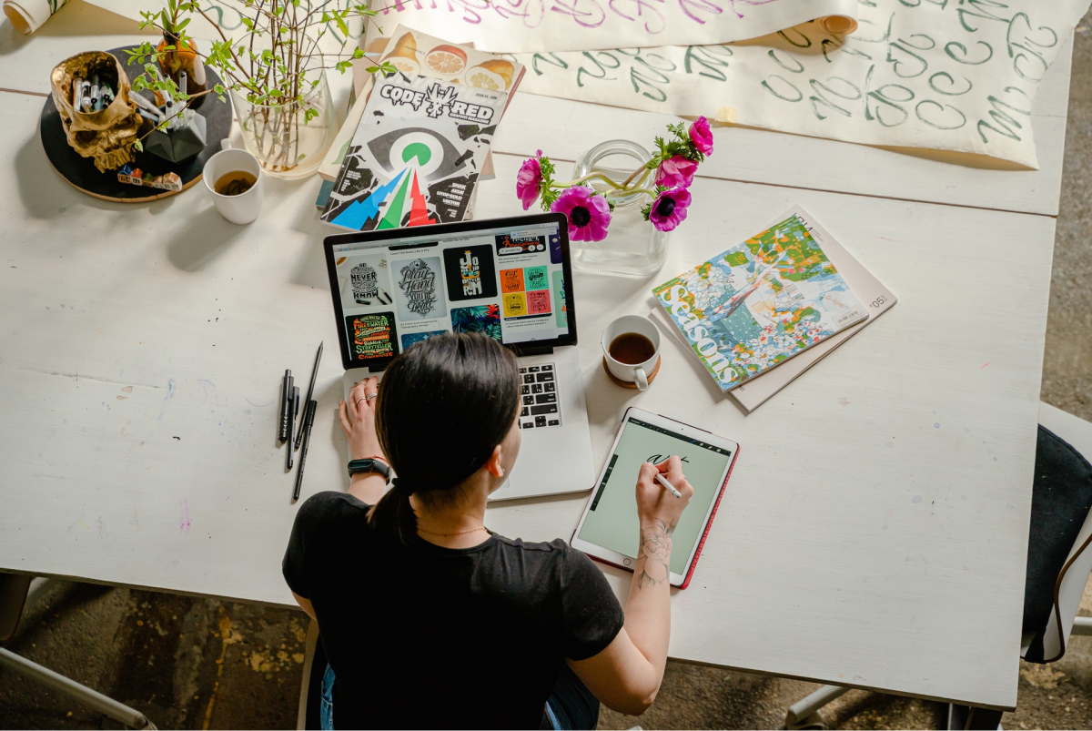 An aerial view of a woman designing on her laptop and tablet on a table.
